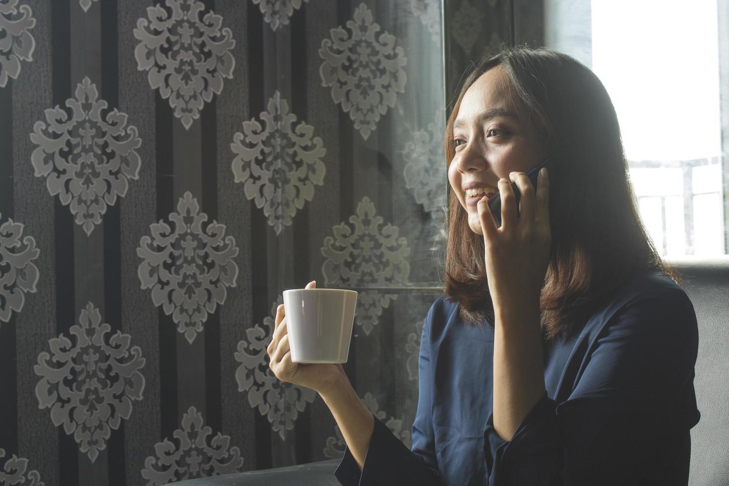 Smilling relajado mujer asiática bebiendo café mientras llama por trabajo foto