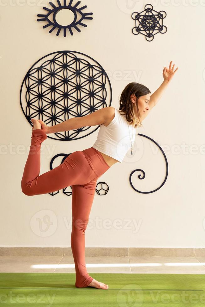 Mujer joven practica asanas de yoga con ropa deportiva foto