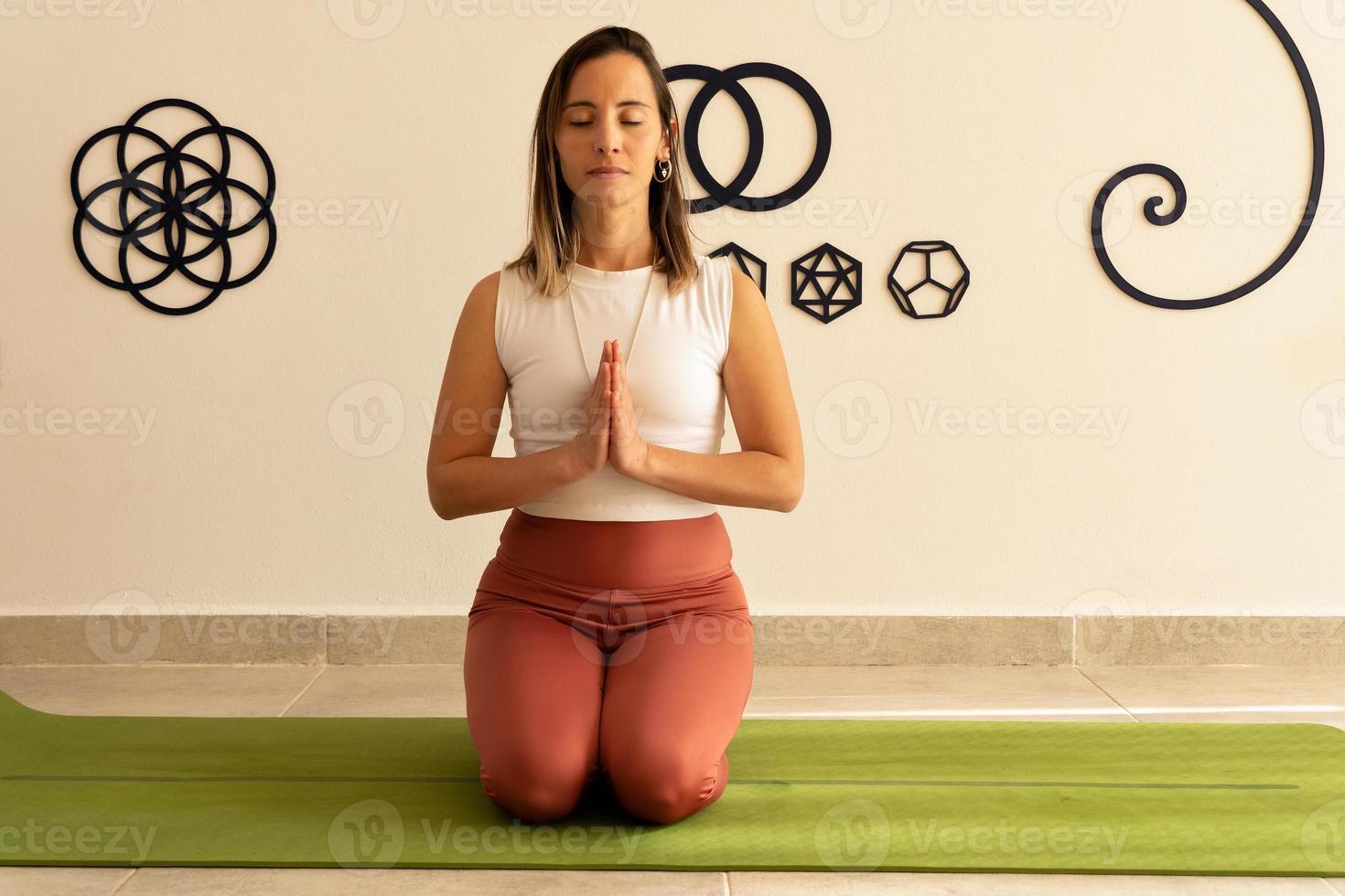 Mujer joven meditando con las manos en posición de oración foto