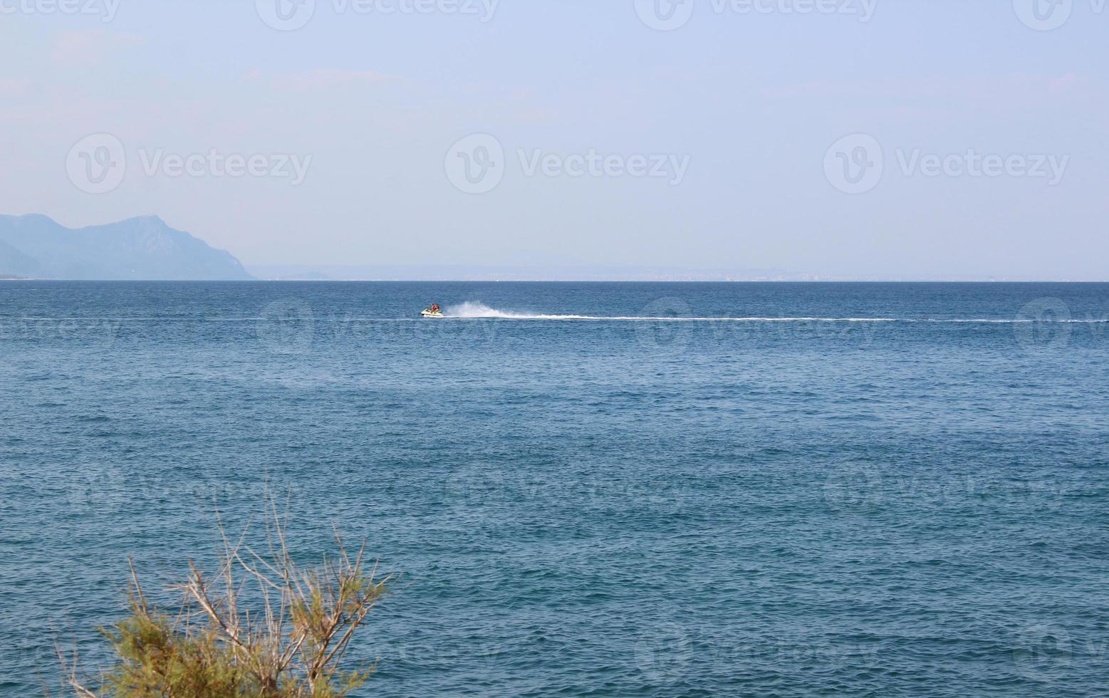 paisaje marino con montañas y gente en una moto de agua foto