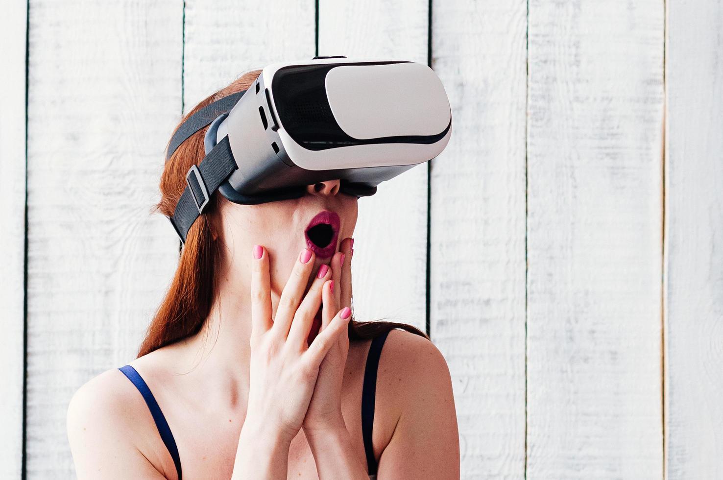 Chica con gafas de realidad virtual, emocionada, sosteniendo sus manos en la cara. foto