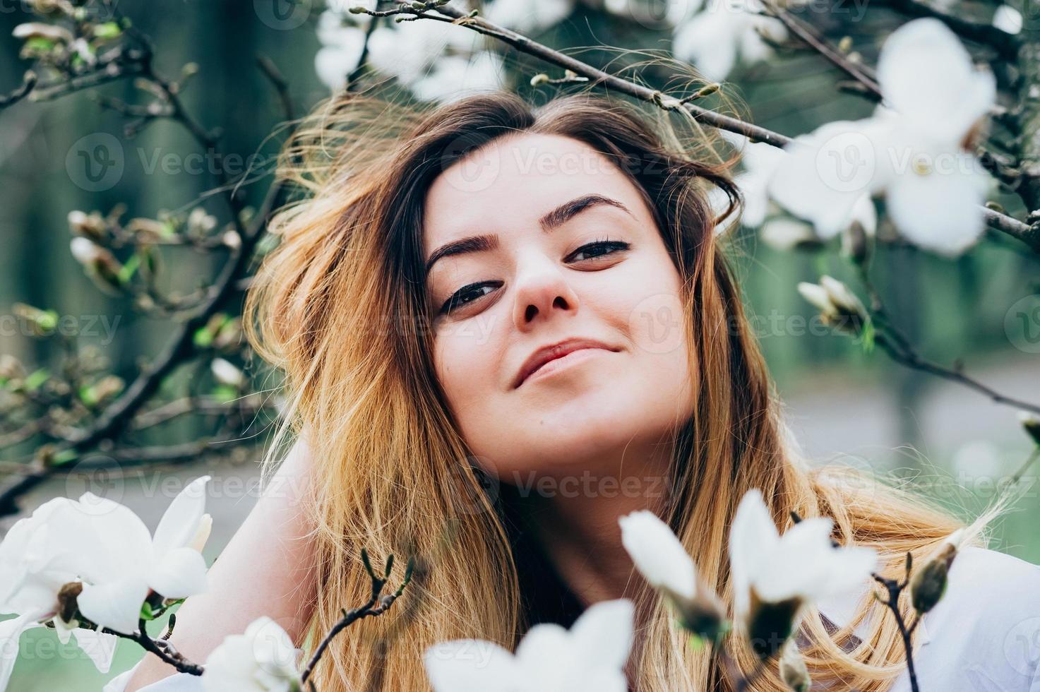 Chica guapa en el jardín disfruta de árboles de magnolia en flor foto
