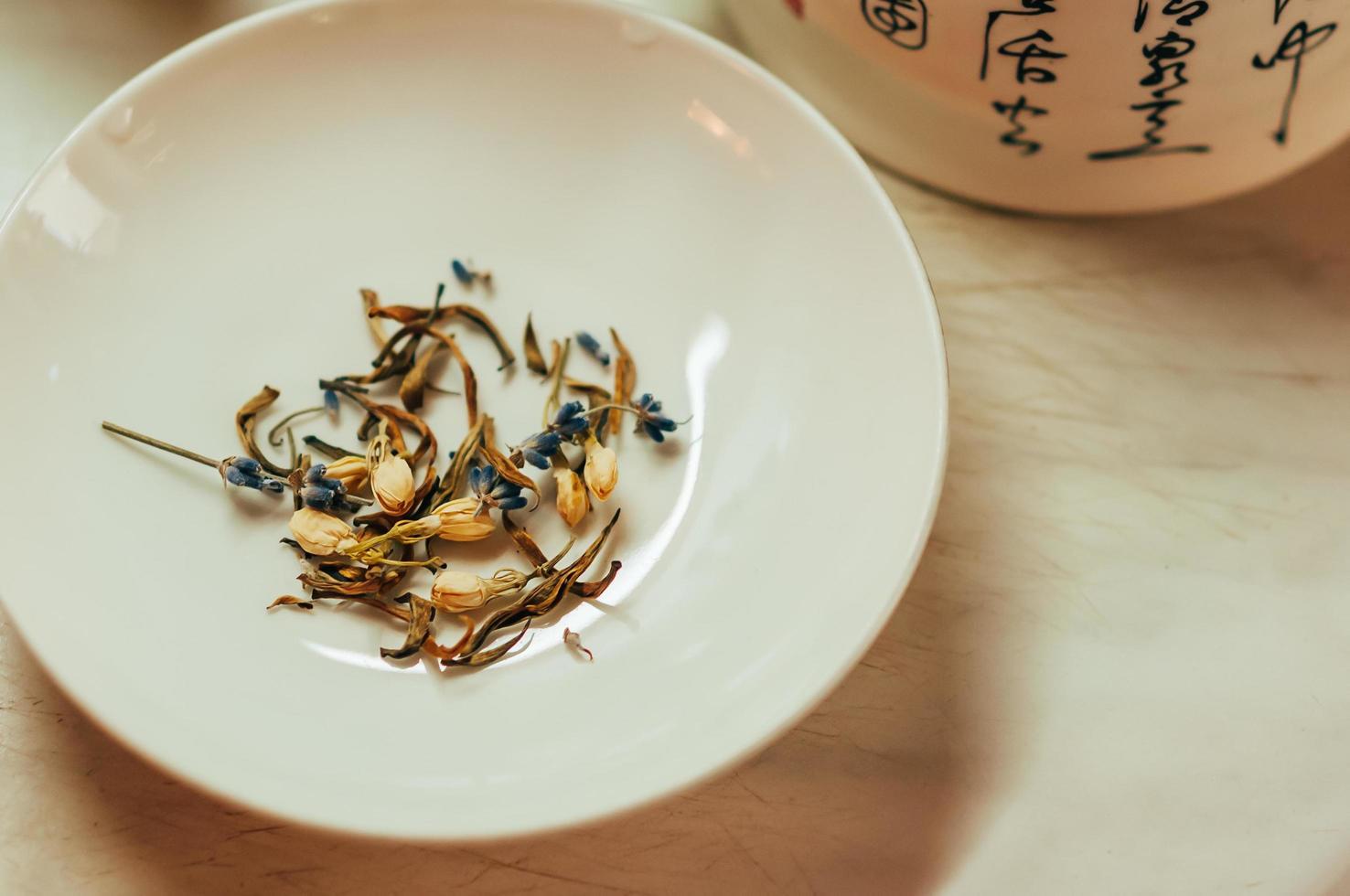 Flores de té de lavanda y jazmín en un platillo foto