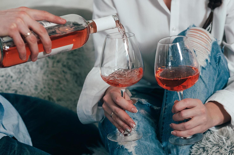 un hombre llena vasos con vino rosado de una botella foto