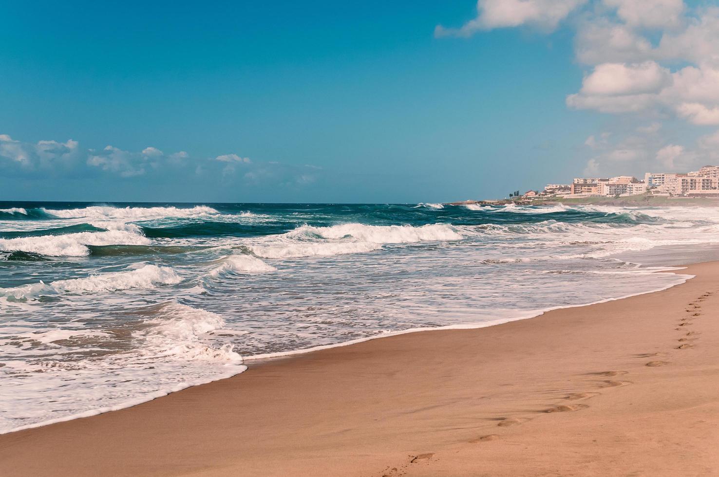 playa paradisíaca del océano, huellas en la arena mojada, hoteles distantes foto