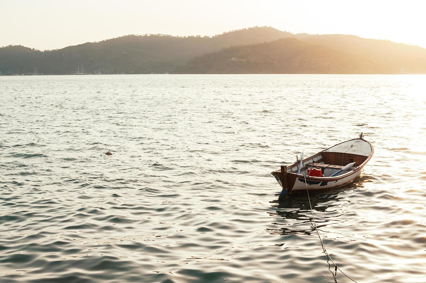 Viejo bote de remos de madera sobre el agua al atardecer foto