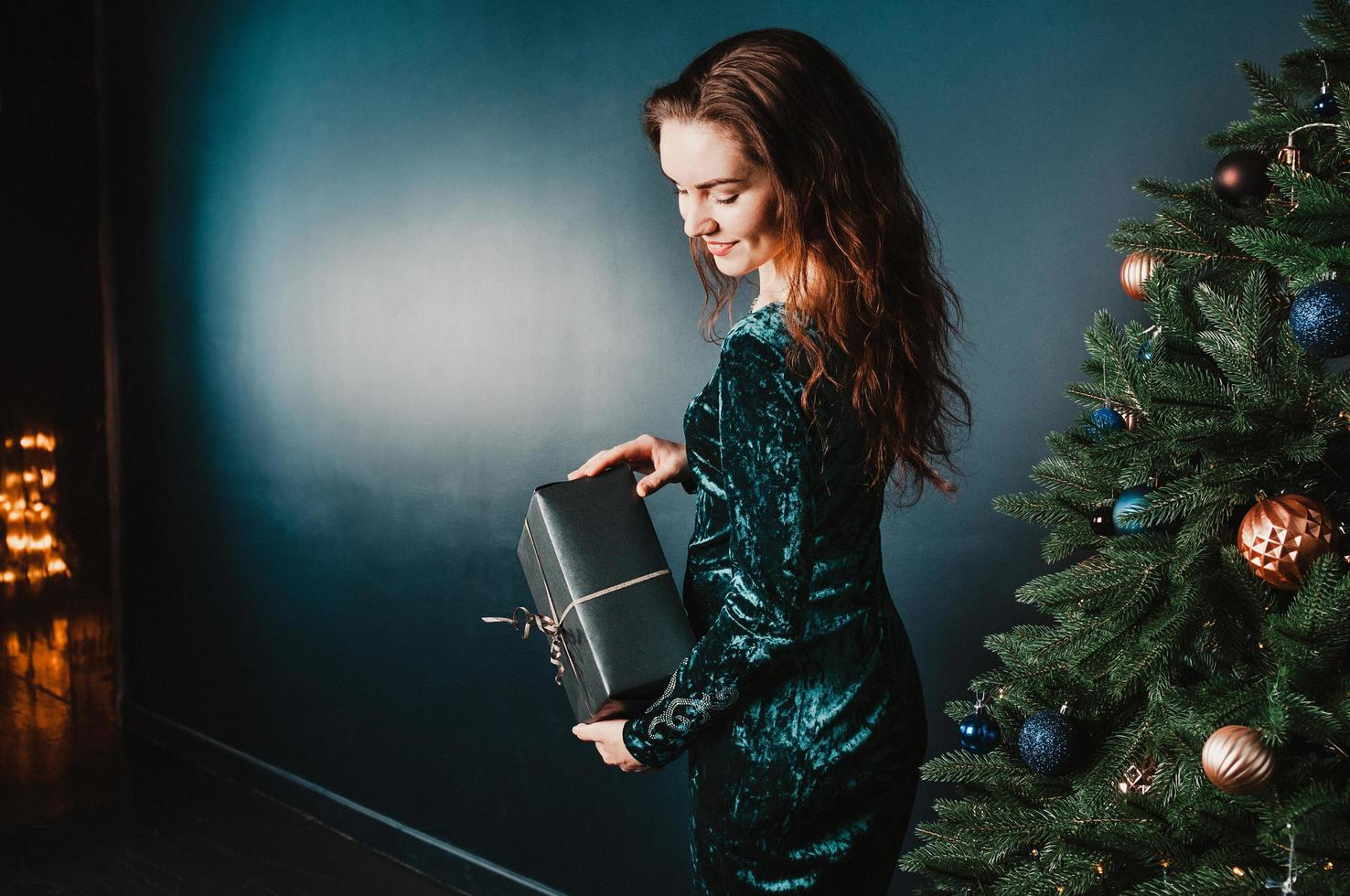 hermosa niña sosteniendo una caja de regalo cerca del árbol de navidad foto