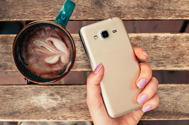 Mano femenina sosteniendo un teléfono inteligente en el café, con capuchino en la mesa foto