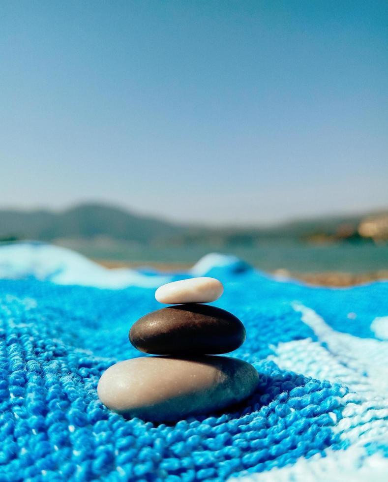 Pila de guijarros en la playa sobre una toalla azul foto