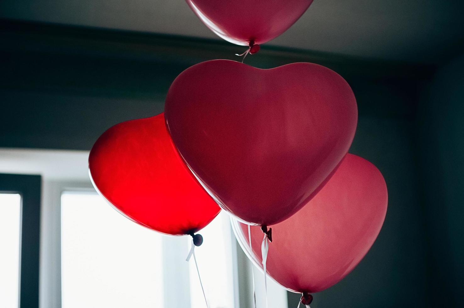 Globos en forma de corazón rojo vintage contra la ventana foto