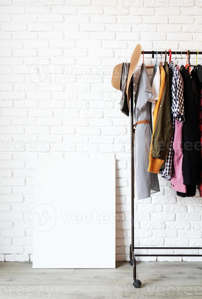 Rack with colorful clothes on hangers and frame canvas for mock up photo