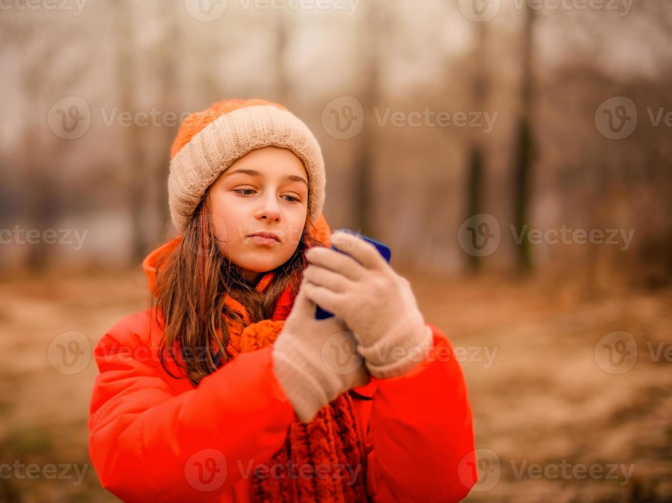 Teenage girl looks into a smartphone in autumn or winter in the park. photo