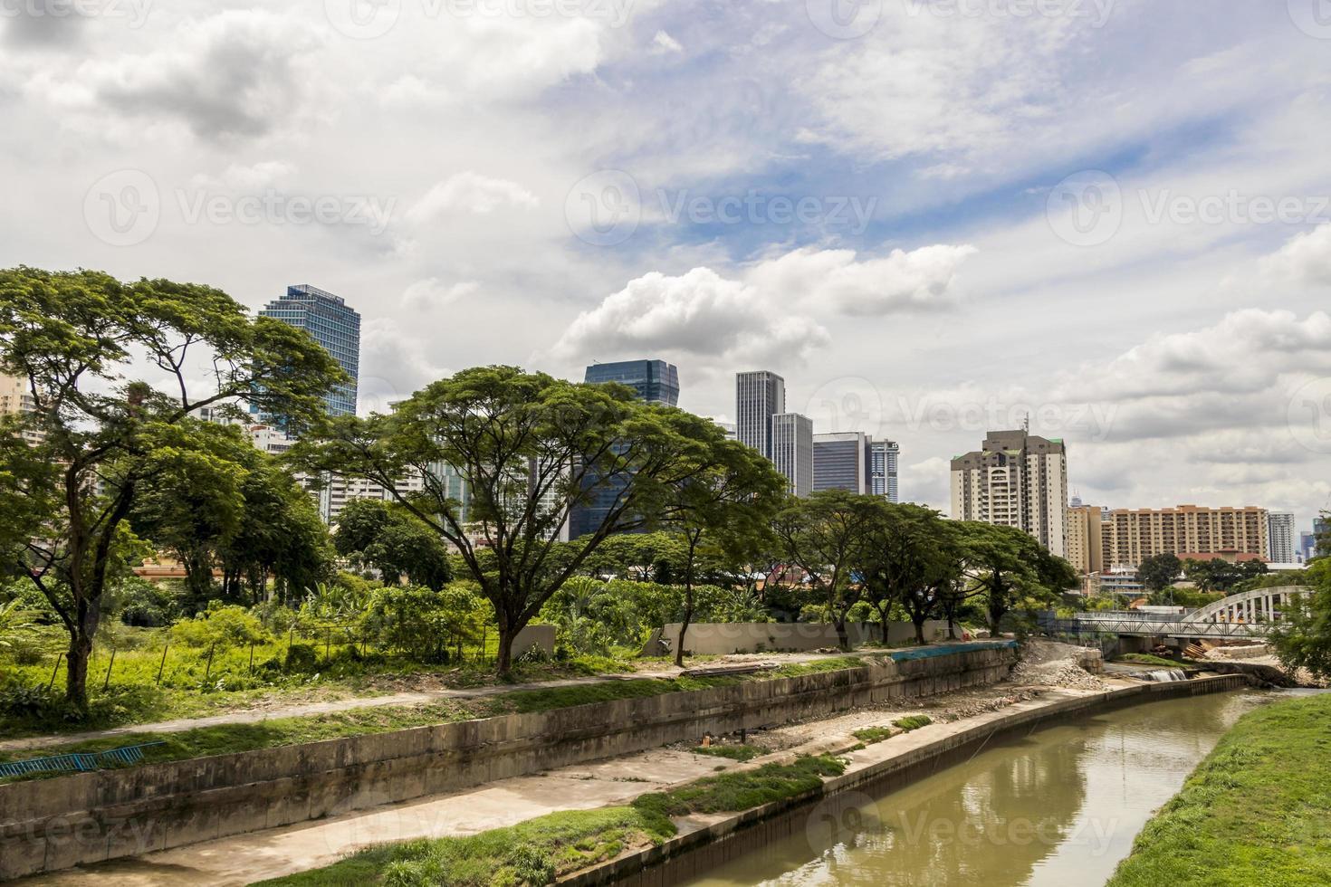 Huge skyscrapers behind tropical nature and river, Kuala Lumpur. photo