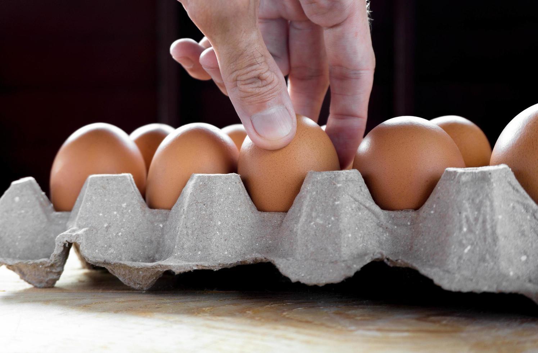 Hombre sujetando huevo de gallina fresco en paquete sobre mesa de madera foto