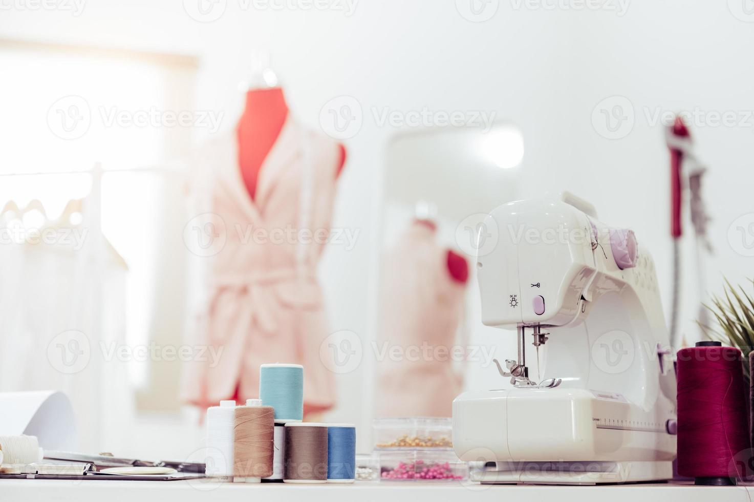 Closeup of sewing machine with fashion designer photo
