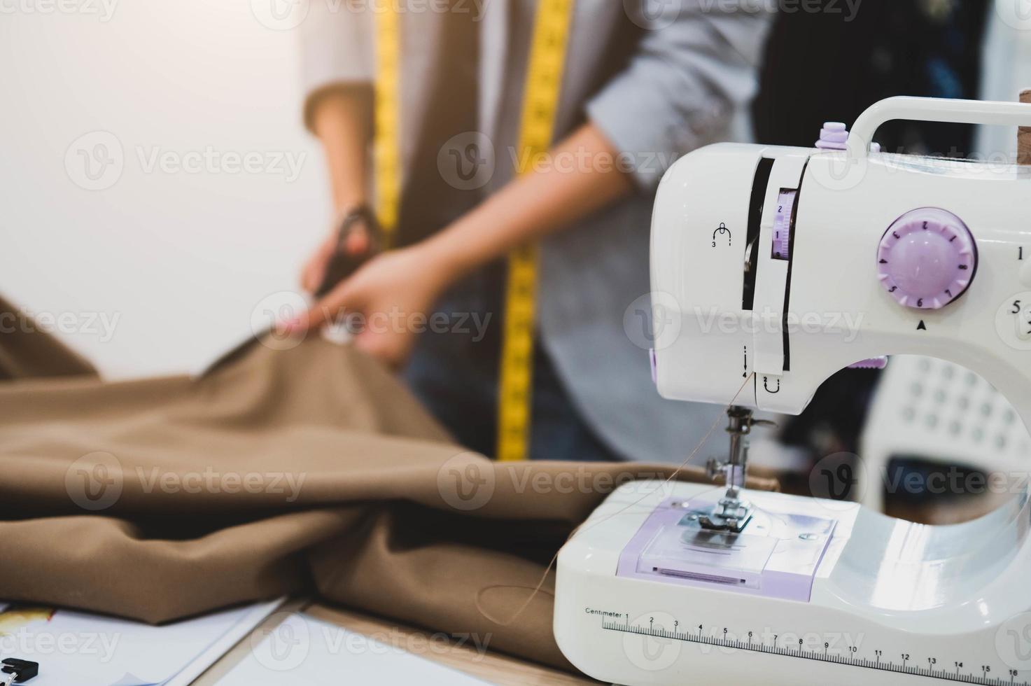 Dressmaker cutting dress fabric on sketch line photo