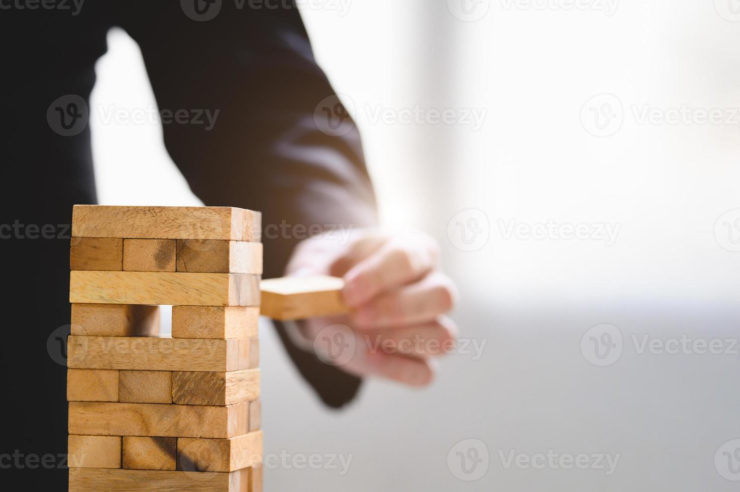 Businessman take and picking one wood block on stacked tower photo