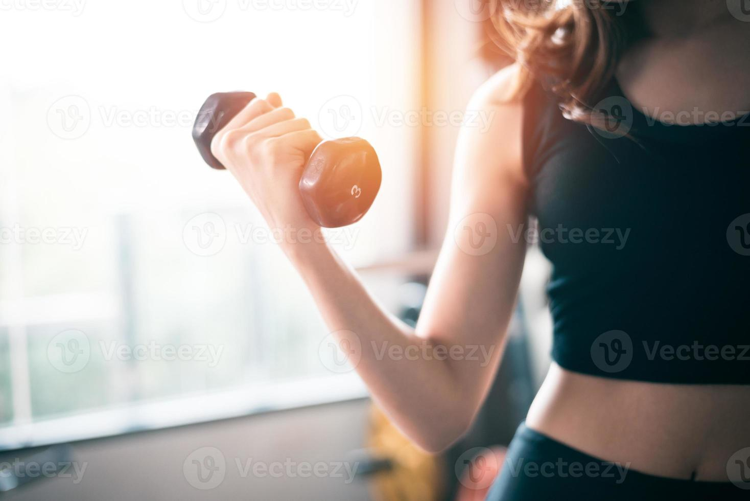 Hand of sports woman lifting dumbbell photo
