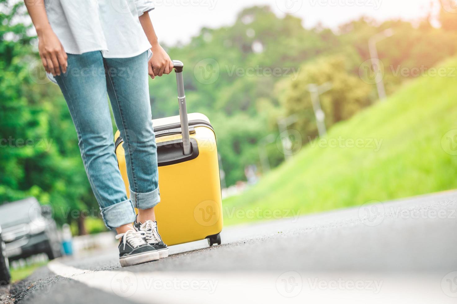 Closeup lower body of woman handling yellow trolly luggage along road photo