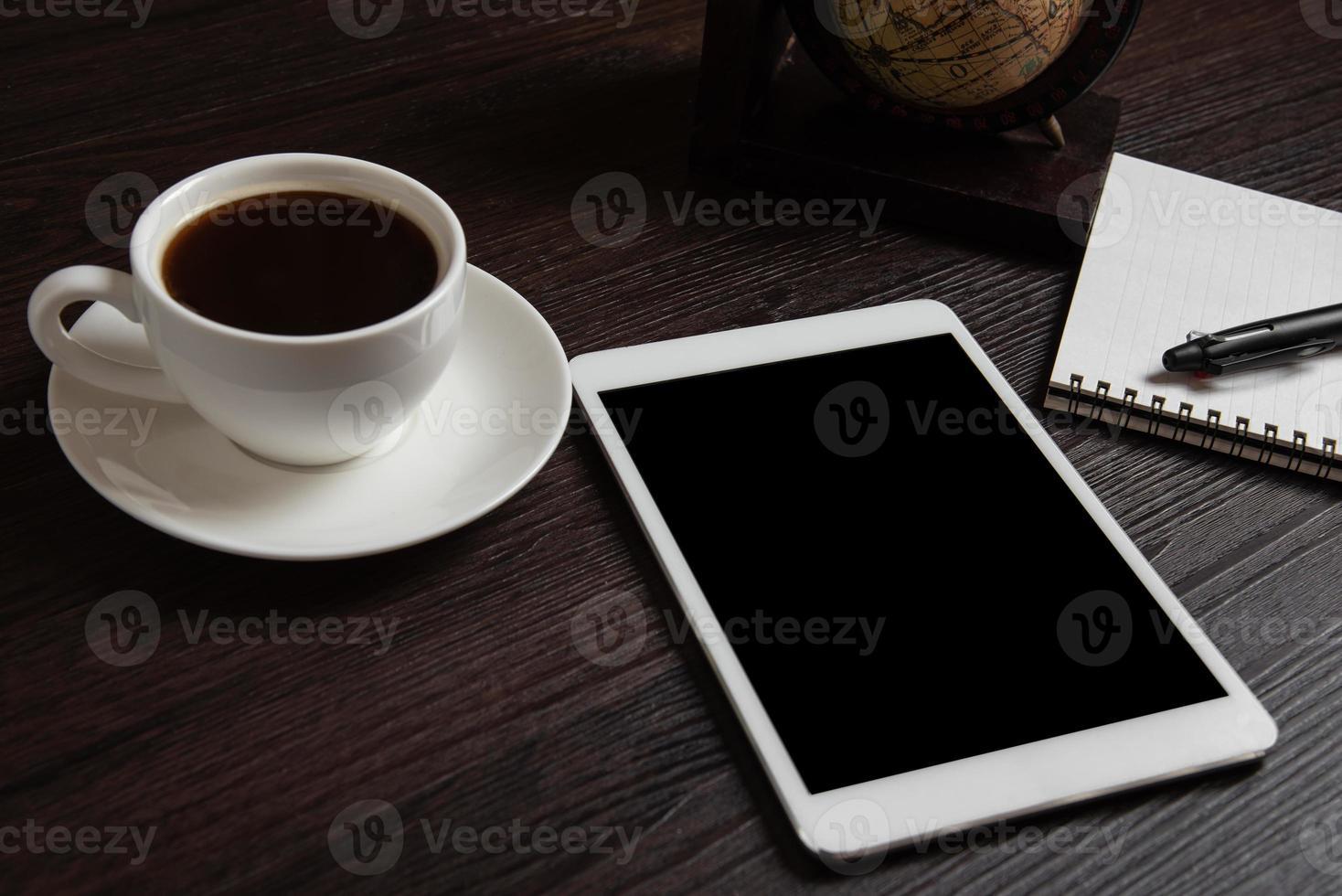 tableta y taza de café y cuaderno en blanco para memo foto