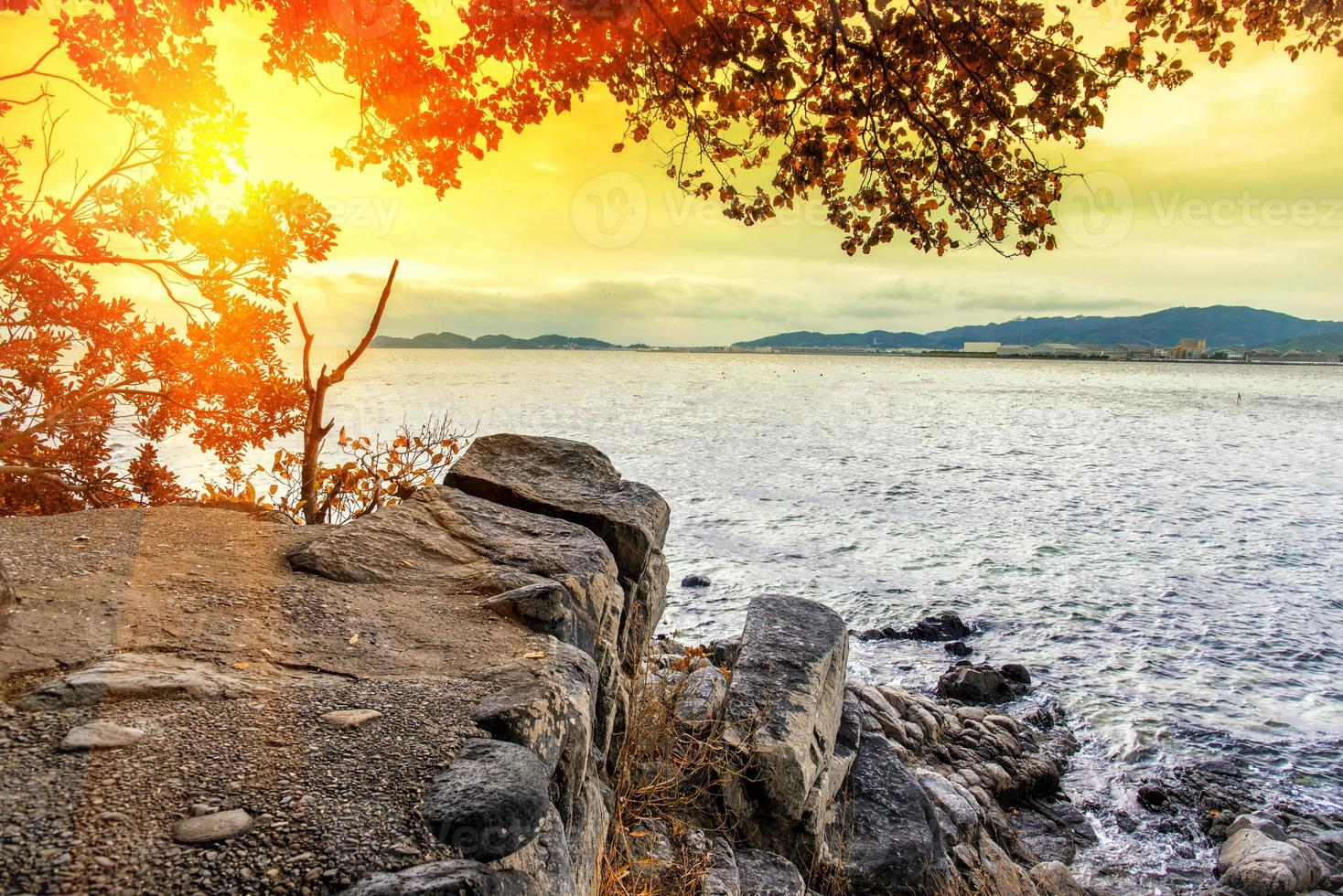 Cliff mountain beside the sea with sun light photo