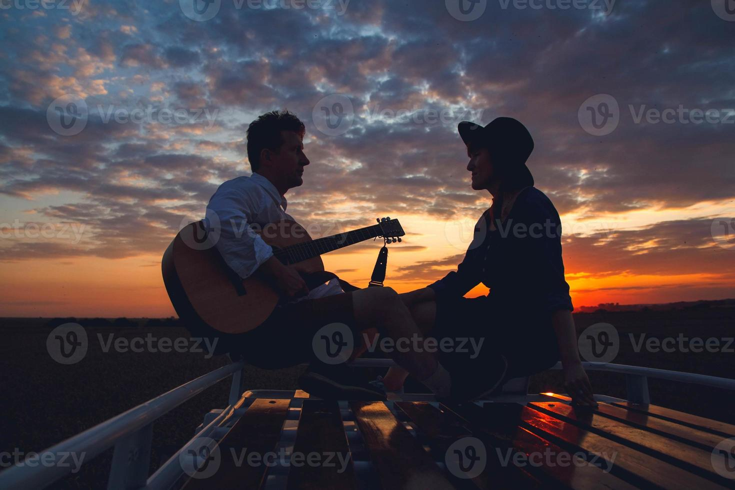 Silhouette of man with guitar and woman on roof of a car on sunset photo