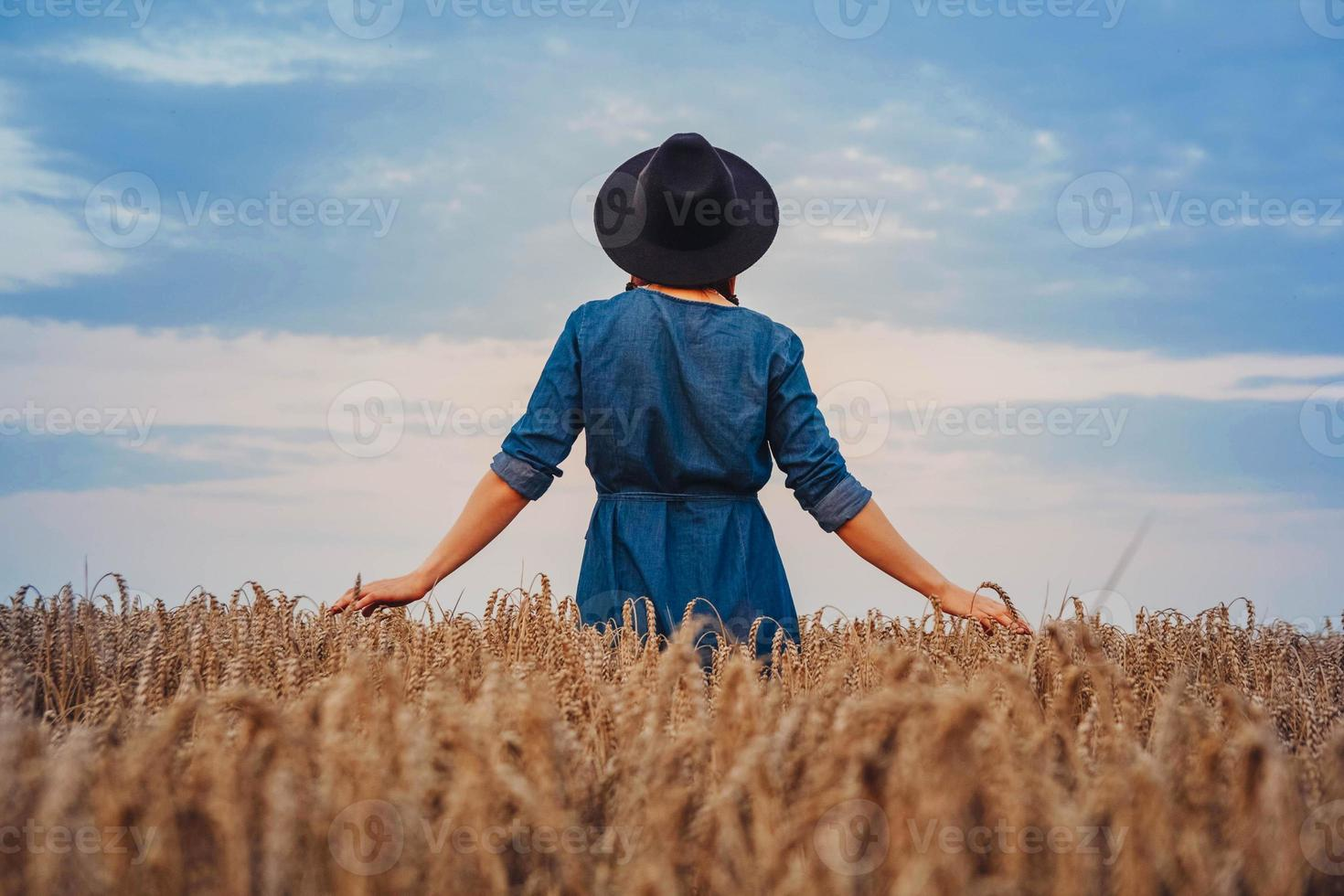 woman in a dress and hat walking through wheat field photo