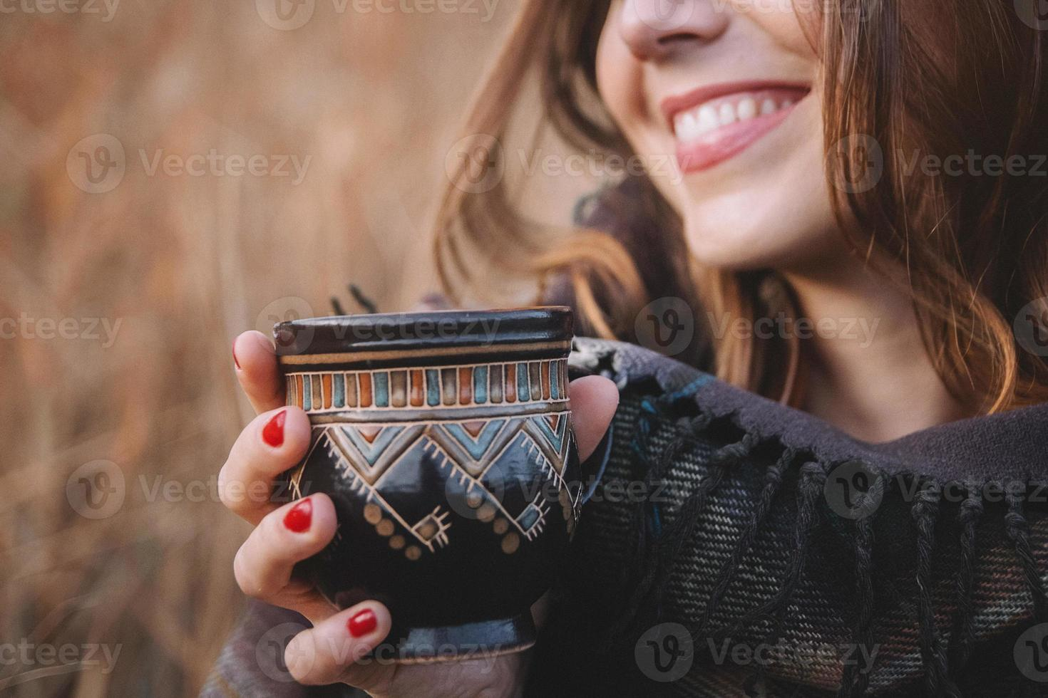 Beautiful woman smiles and holds a cup with a drink photo