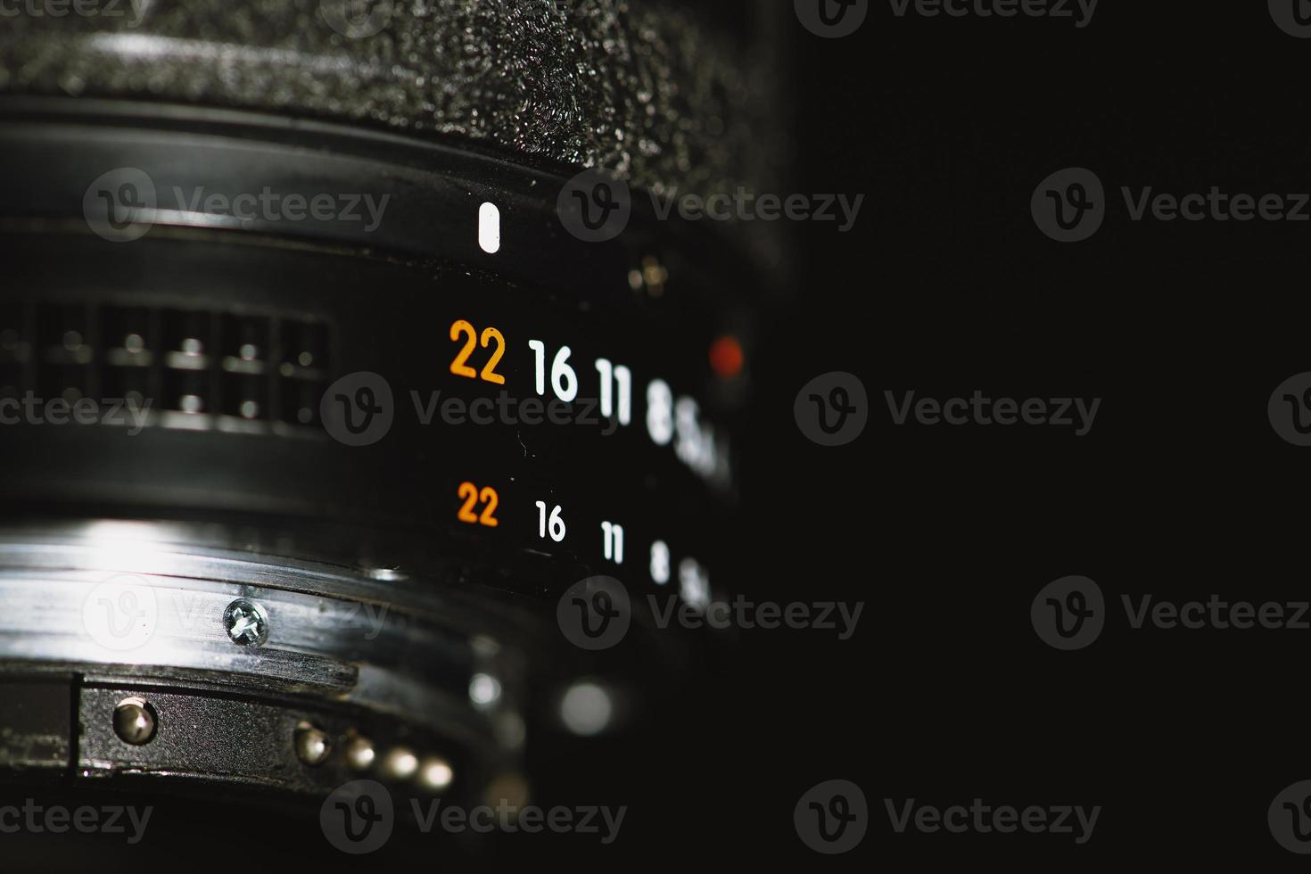 Camera lens with aperture numbers on a black background photo