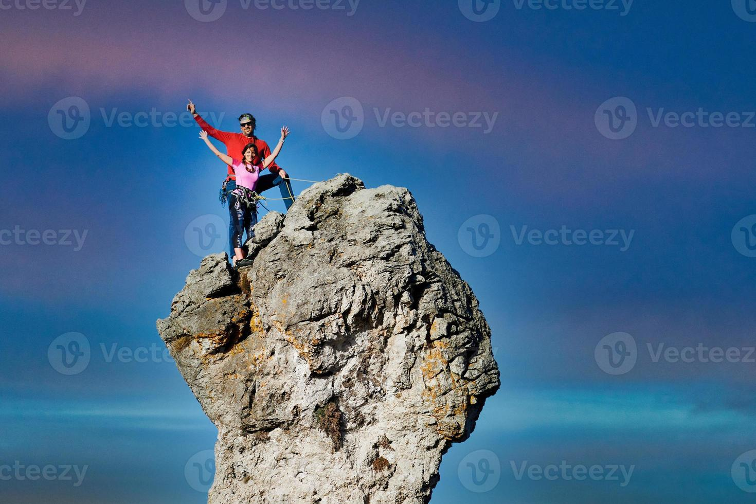 Two male and female climbers on top of a rocky peak photo