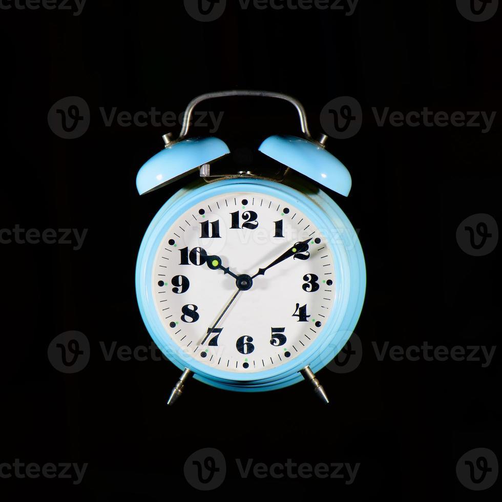 Classic table alarm clock light blue on a black background photo