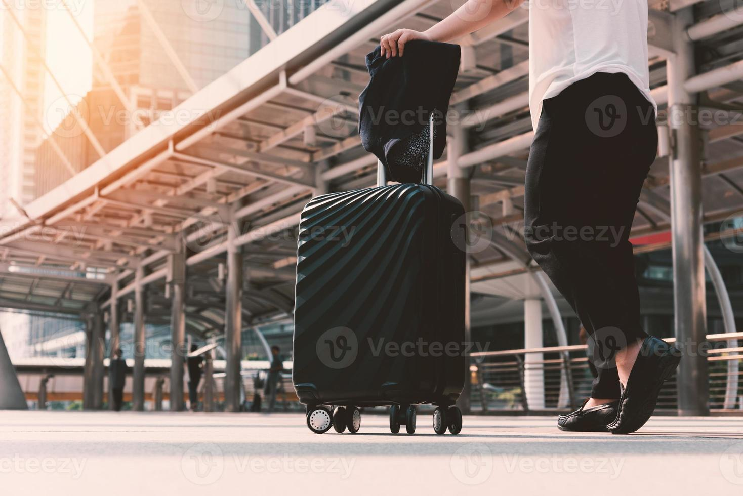 Asian woman walking to airport terminal with luggage photo