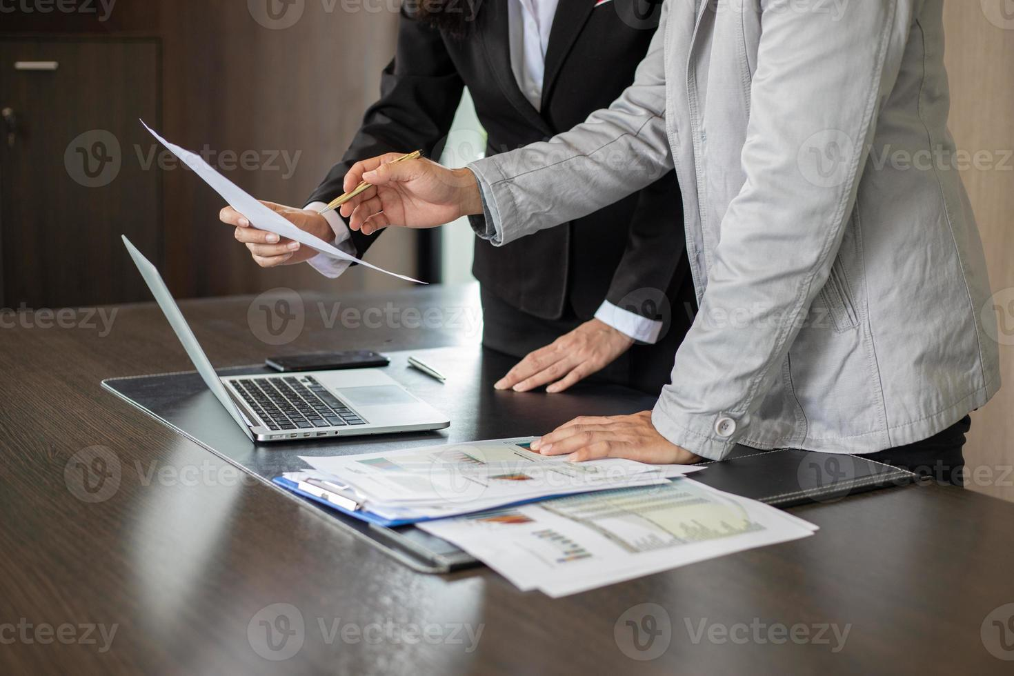 Businesswoman and businessman analysing documents photo