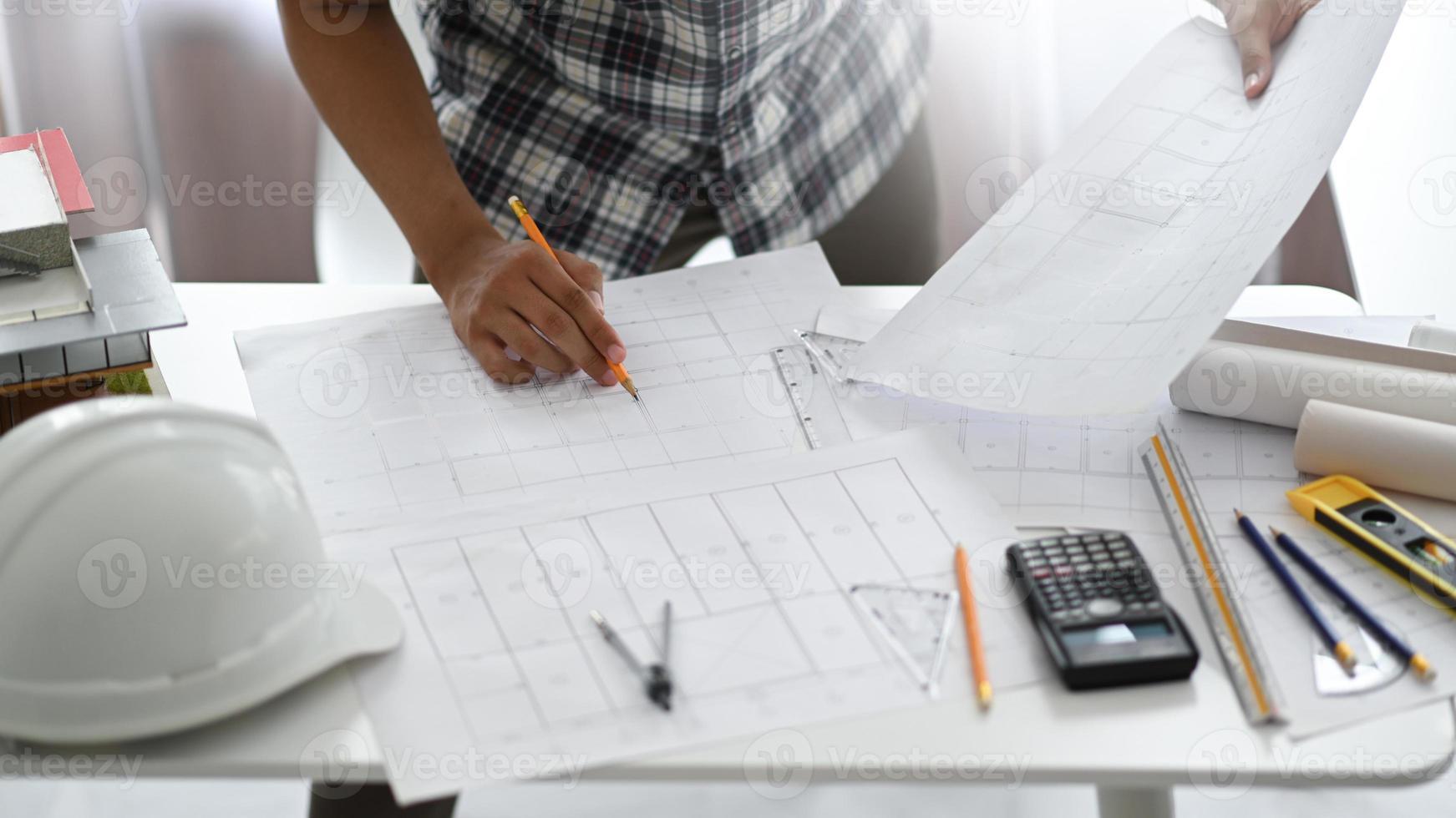 hombre diseñador que sostiene un lápiz examinando planos de la casa. foto