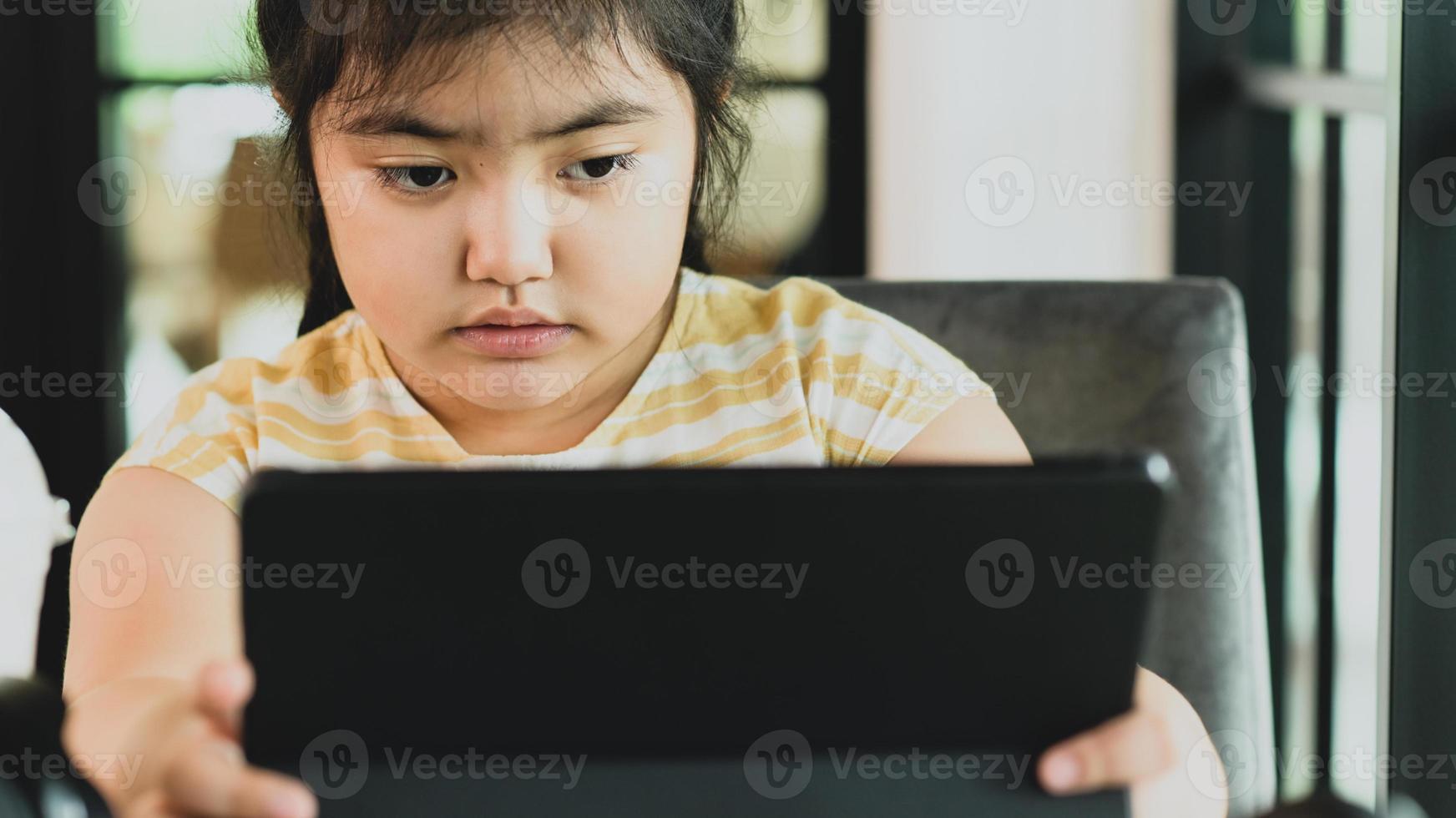 niña miró la tableta con los ojos cansados de estudiar en línea. foto