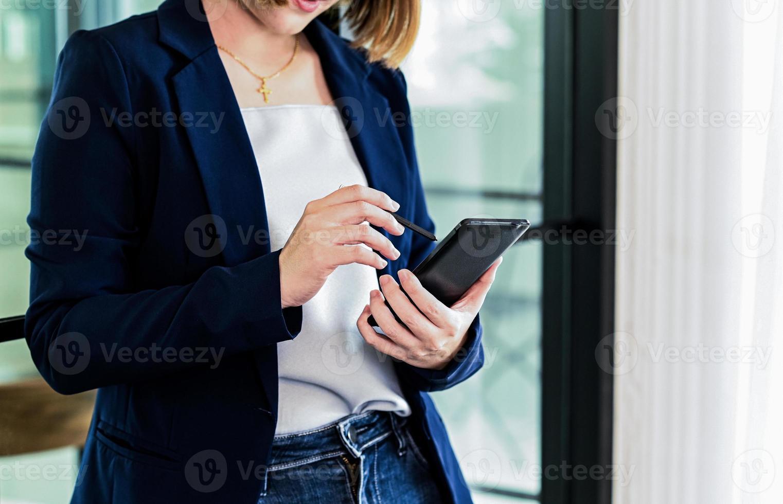 mano de mujeres empresarias con lápiz en el teléfono inteligente. foto