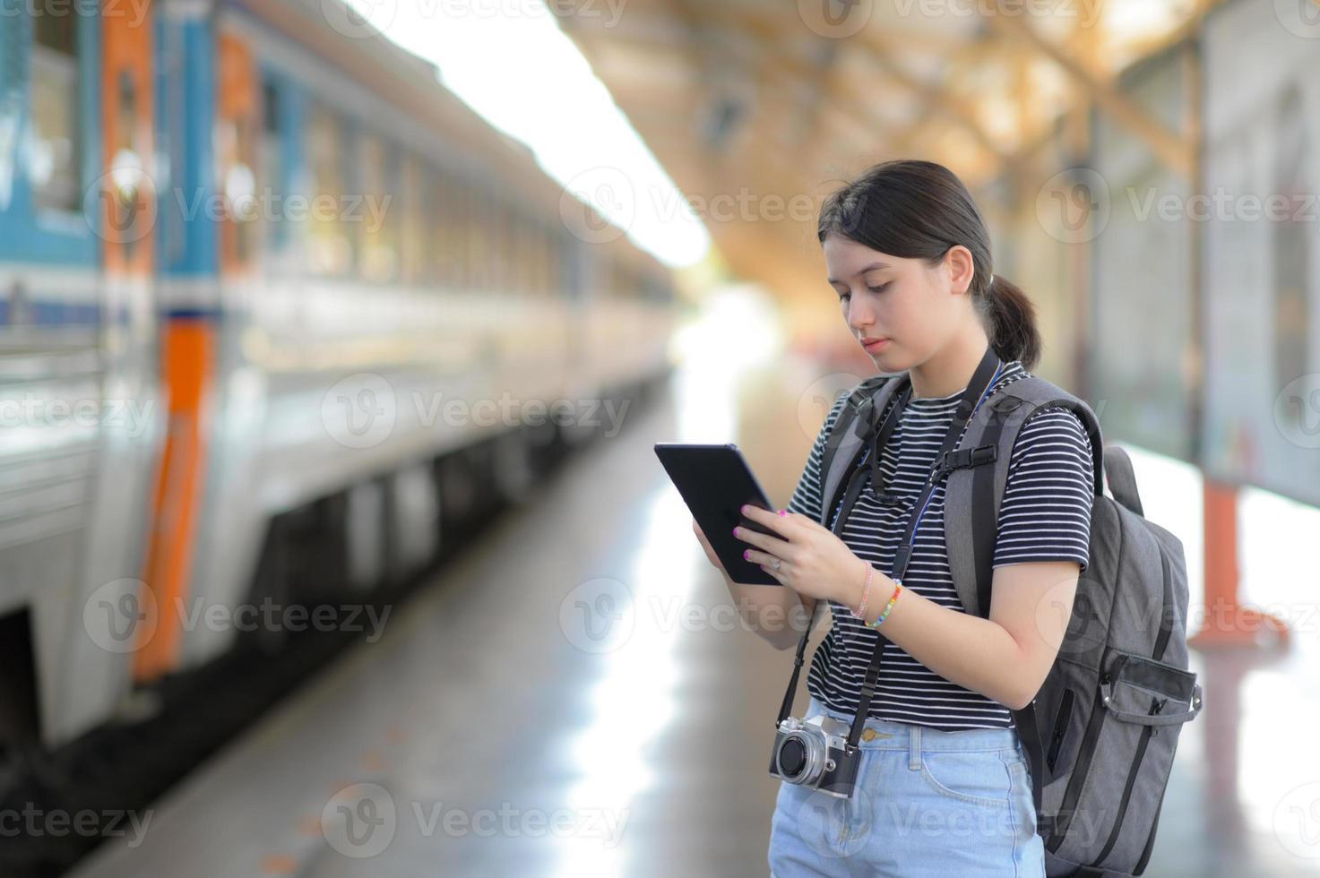 Una viajera extranjera lleva una mochila con una tableta mientras espera el tren. foto