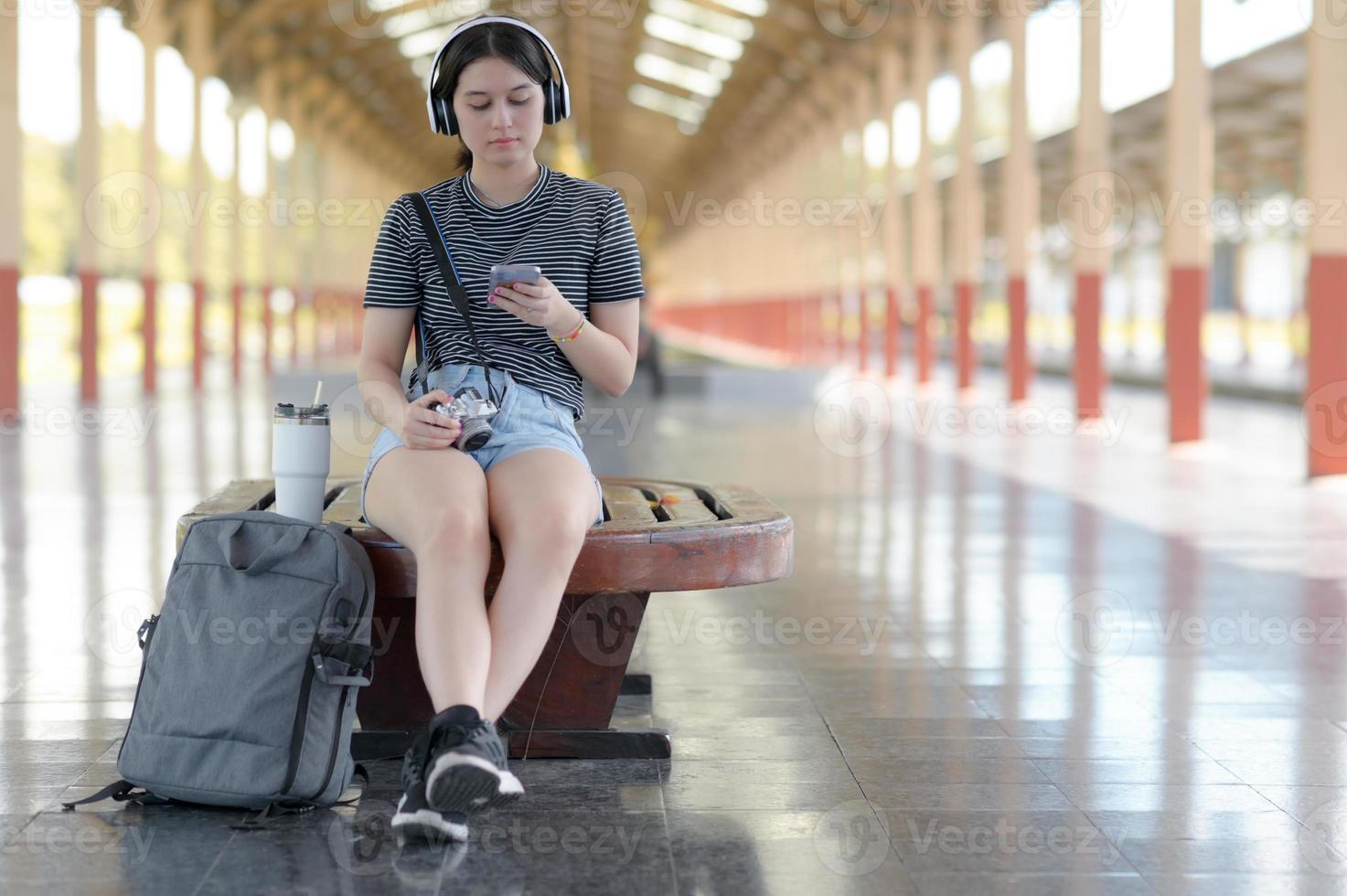 una joven viajera escucha música con auriculares mientras espera su viaje en la plataforma. foto