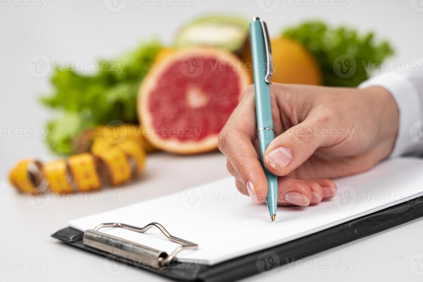 mujer escribiendo, frutas borrosas en el fondo foto