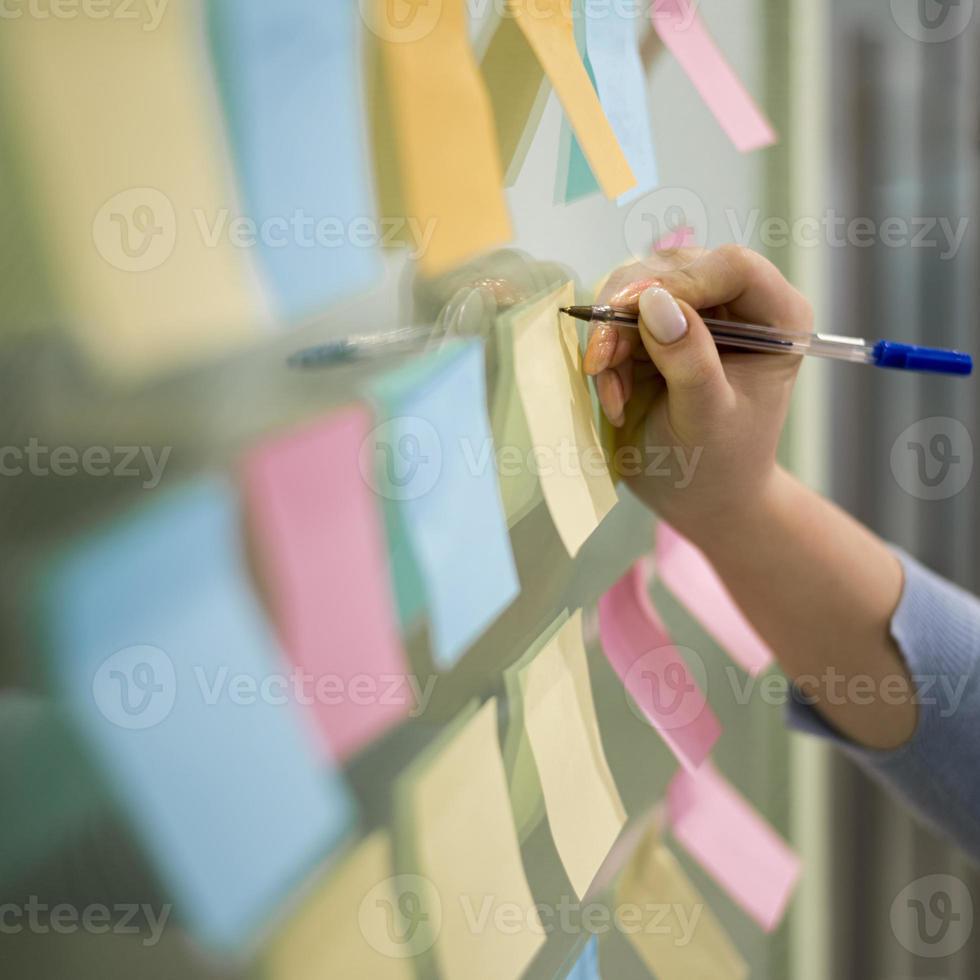 Mujer escribiendo notas adhesivas en la ventana de la oficina foto
