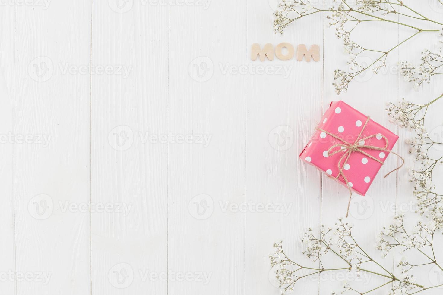 palabra mamá con caja de regalo y flores foto