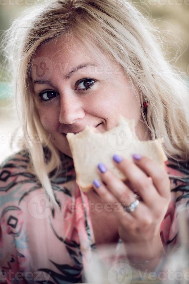 mujer rubia sosteniendo y comiendo un sándwich, mirando a la cámara. cerrar sesión de retrato. foto
