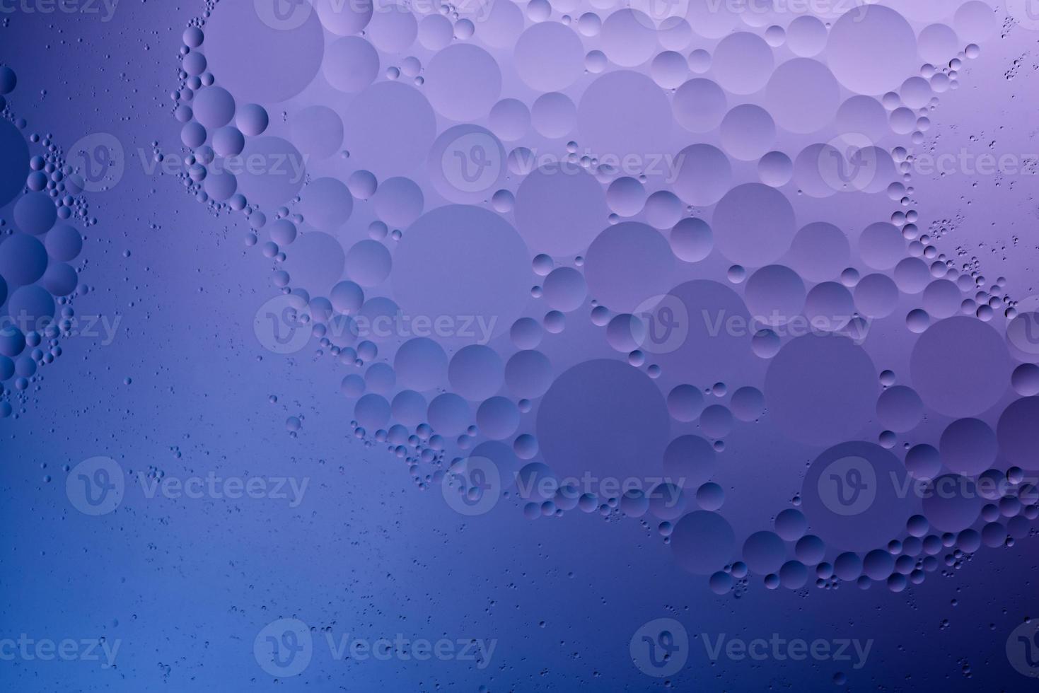 agua y aceite, fondo abstracto de color basado en círculos y óvalos de color azul, morado y neón, abstracción macro, foto real.