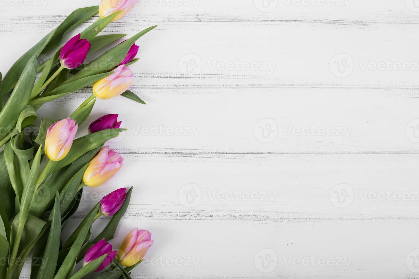 tulipanes de colores sobre fondo de madera foto