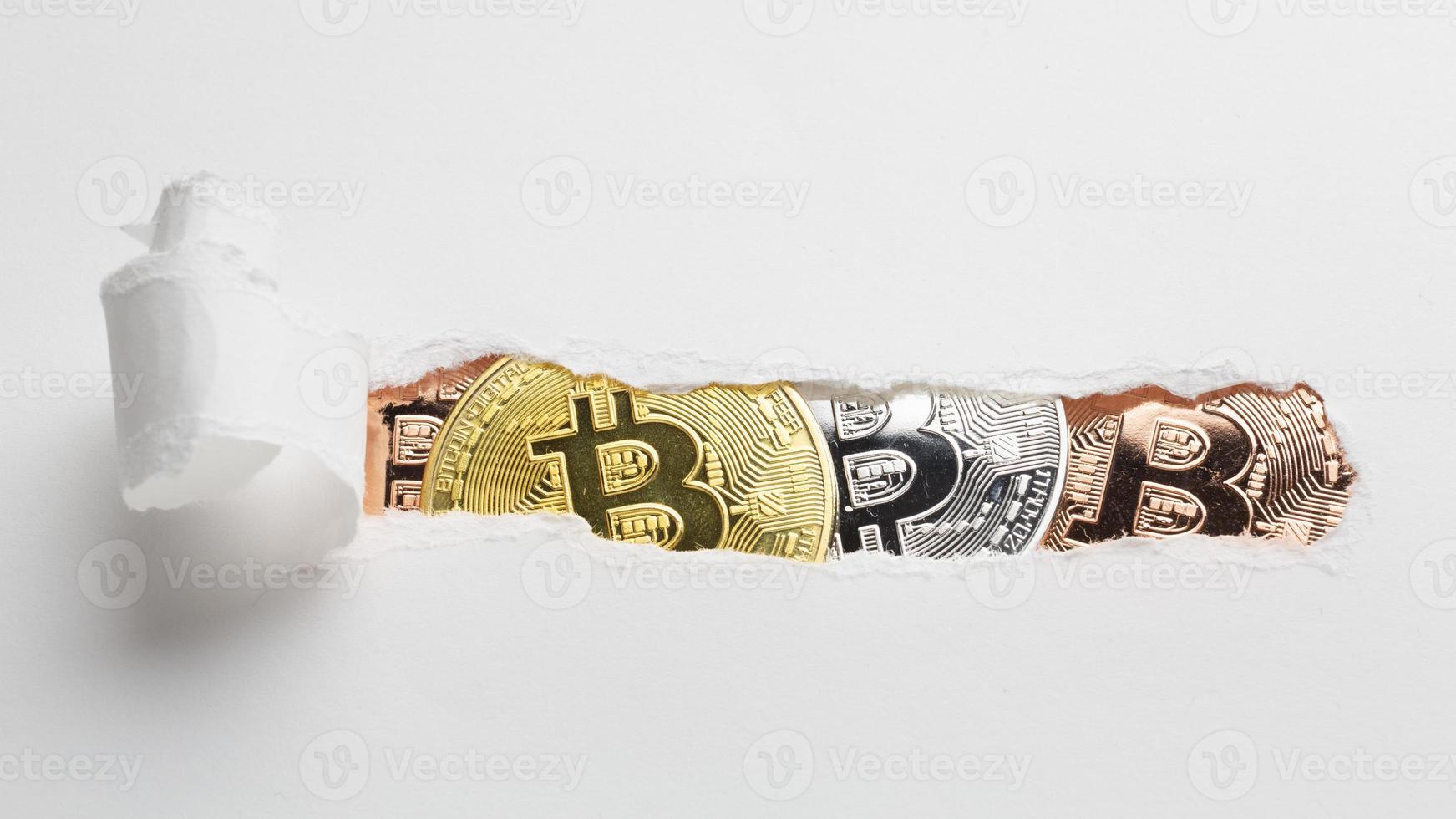 papel rasgado que revela bitcoin foto