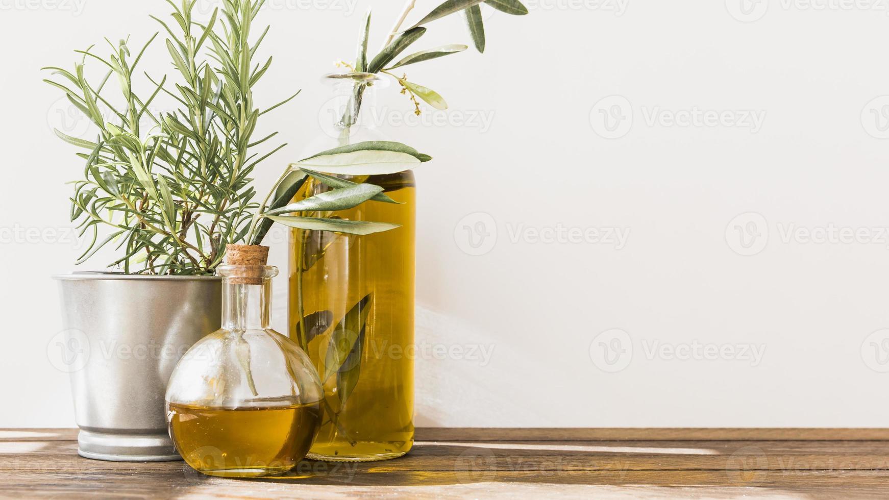 Romero con botellas de aceite de oliva en la mesa de madera foto
