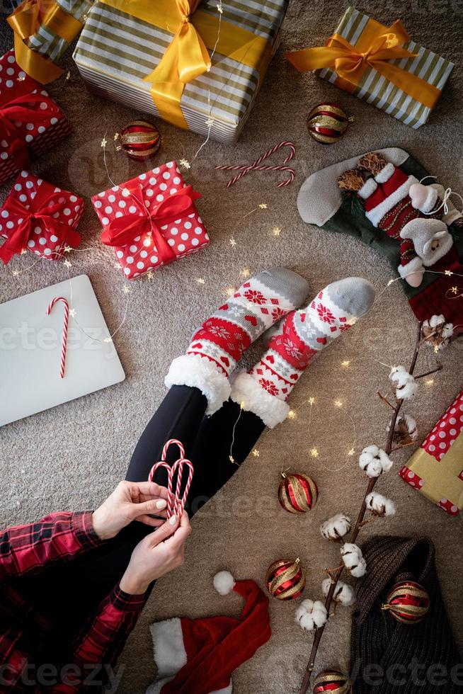Top view of woman in funny socks celebrating Christmas at home photo