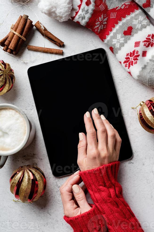 Christmas desktop with tablet surrounded by coffee, stockings photo