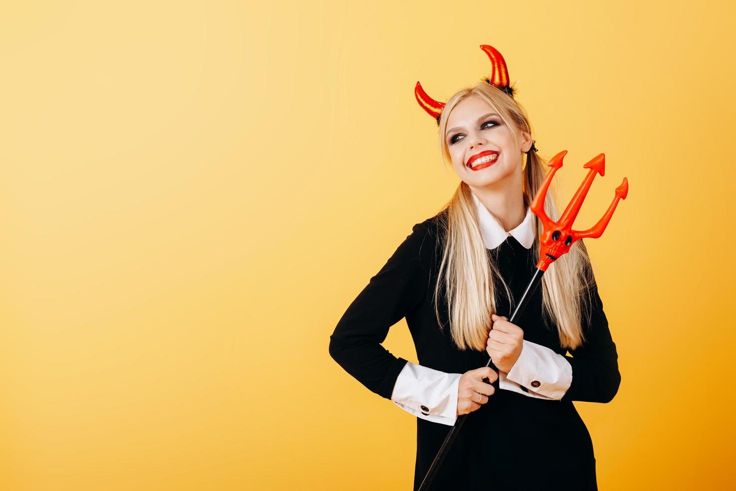 Happy emotion of devil woman standing against a yellow background . photo