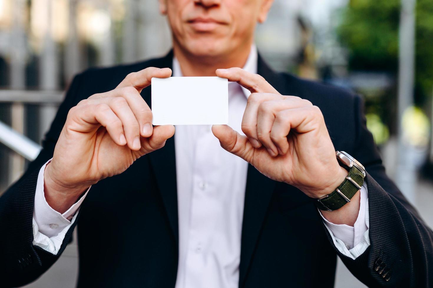 Primer plano blanco vacío maqueta en blanco de tarjeta de visita en manos masculinas - espacio de copia foto